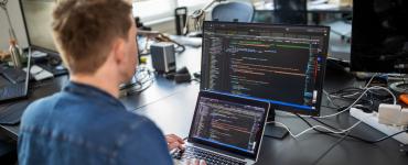 Ein Entwickler sitzt an seinem Laptop und programmiert an einer Anwendung.